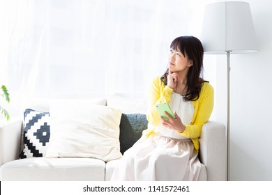 Asian middle age woman who uses smart phone,think,