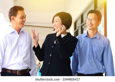 Asian middle aged business team having conversation while walking