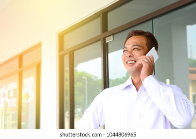 Asian middle aged businessman talking on the smartphone