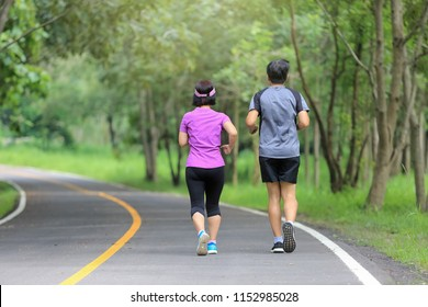 Asian middle aged couple jogging and running in park
