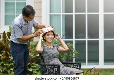 Asian middle aged couple sitting and relax in backyard