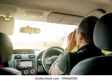 Asian middle aged man drinking coffee while driving his car. Focus on hand holding coffee cup.