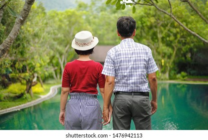 Asian middle aged man relaxing with his wife in anniversary wedding day