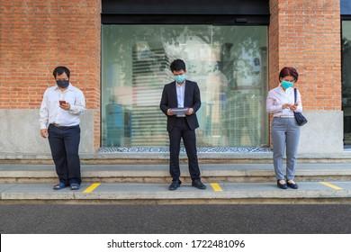 COVID-19の普及を避けるため、マスクを着て社会的距離を保つアジアの中年の人々