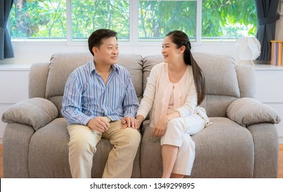Asian middle-aged couples, men holding a female hand, sending their eyes to each other in the room, they are flirting