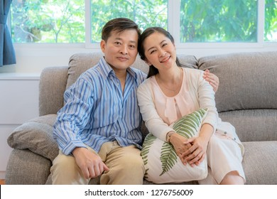Asian middle-aged couples sit and relax on the sofa in the living room.
