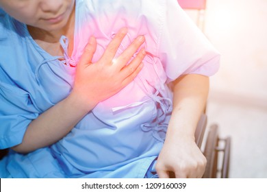 Asian middle-aged lady woman patient chest pain may be a symptom of heart attack in the hospital ward : healthy medical concept