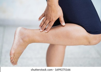 Asian middle-aged lady woman patient touch and feel pain her leg : healthy medical concept.