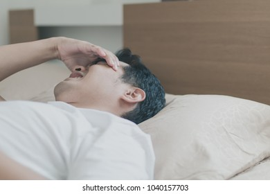 Asian middle-aged man suffering from migraine while sleeping on his bed