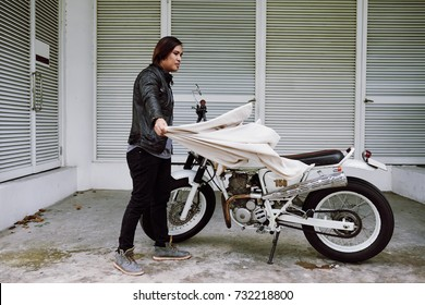 Asian middle-aged man wearing stylish clothes removing cover from vintage motorcycle while preparing for trip