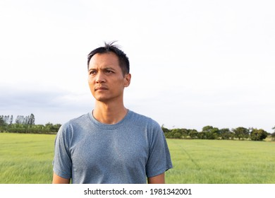 Asian middle-aged men, aged 45 to 50, stand looking at the sky in the field with hope. Because the rice fields need rain to grow With a serious expression Because it had not rained for a long time .