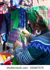 Asian minority woman choosing colorful handicraft textile product at a traditional flea market.