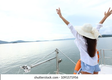 Asian Mix Race Tanned skin Woman Bikini White Shirt Big Hat short jean stand on deck of Yacht Boat with orange life buoy under summer blue sky in vacation holiday, copy space text logo