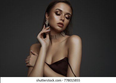 Asian model fashion girl with tassel earrings and gold choker,neck.Fashionable woman in black coat copy-space, looking at camera. cold season. Autumn or winter look.present for her,gold,silver