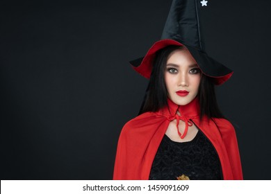 Asian model. Halloween Witch with a Witch broom . Beautiful young woman in witches hat  costume  and holding evil halloween craved pumkin. Wide Halloween party art design with black background.