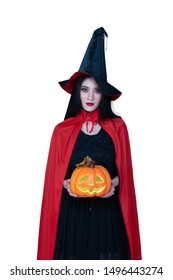 Asian model. Halloween Witch with a Witch broom . Beautiful young woman in witches hat  costume  and holding evil halloween craved pumkin. Wide Halloween party art design with isolated white backgroun