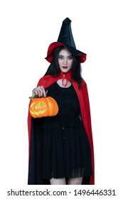 Asian model. Halloween Witch with a Witch broom . Beautiful young woman in witches hat costume  and holding evil halloween craved pumkin. Wide Halloween party art design with isolated white background