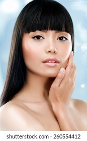 Asian model posing on blue background.