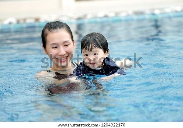 アジアの母子が幸せなプールで泳いでいる
