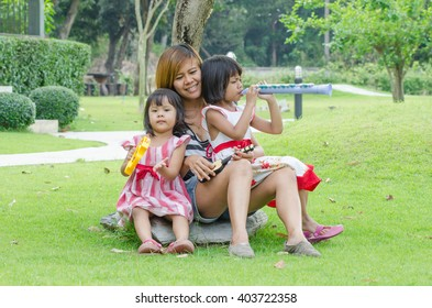 Asian Mom And Child Happy Play Music In The Park