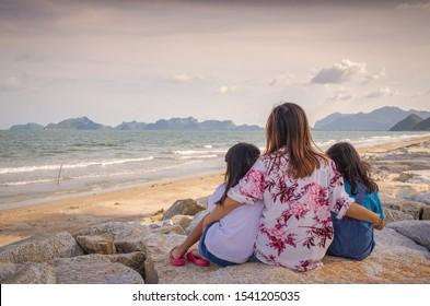 Asian Mom And Child Sad On Beach