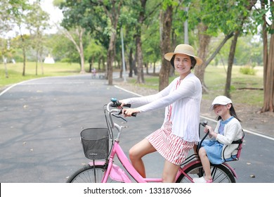 Asian mom and daughter riding bicycle together in park. Happy family.