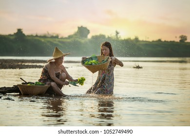 Asian mom and daughter washing vegetable and working together in Mekong river,Nongkhai Thailand.