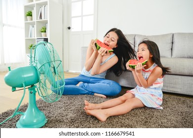 asian mom and girl eating watermelon together. with electric fan blowing their faces. enjoy wonderful time happily.