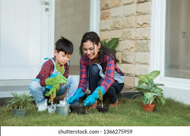 asian mom and her son planting a plant at home garden in the morning together. gardening activity with family
