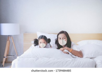 Asian mom and kid with surgical mask on the bed in white bed room, Covid19 pandemic family protection concept