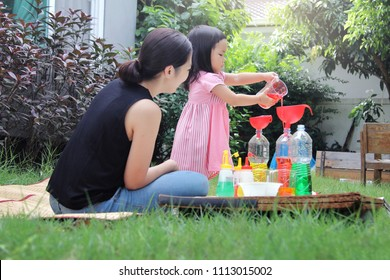Asian mom and little daughter experiment with different water colors mixing for learning and strengthen Imagine.