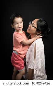 Asian mom plays with her cute mixed race 2 year old boy on a black background
