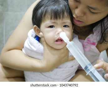 Asian mom rinsing her baby's stuffy nose using a syringe of saline water - effective home remedy for clearing a baby's clogged nose
