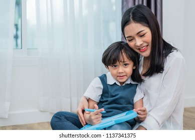 Asian mom teaching cute boy to drawing in chalkboard together. Back to school and Education concept. Family and Home sweet home theme. Preschool kids theme.