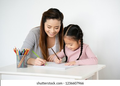 Asian moms are teaching crayon skills to Daughters. To draw a line. Write book on paper Artistic development Imagine And the mood of the children very well. And the family is very understanding love.