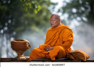 Asian monk meditating under a tree