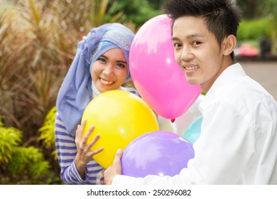 Asian Moslem happy couple with balloon
