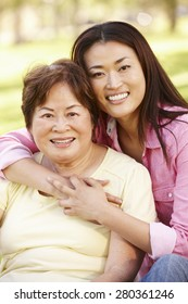 Asian mother and adult daughter portrait outdoors