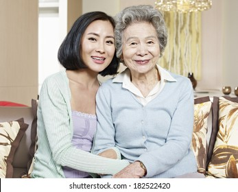 asian mother and adult daughter sitting on couch smiling