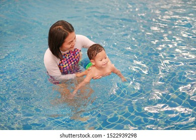 Asian Mother and baby boy relaxing in swimming pool training.