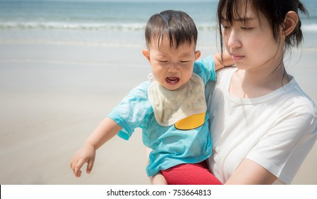 Asian mother and baby Cry on the beach