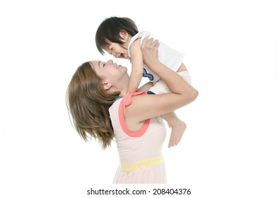 Asian mother and baby kissing, laughing and hugging