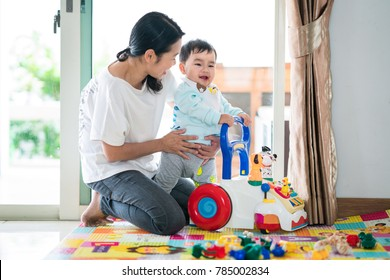 Asian mother and baby training walking with walker toy. This immage can use for baby, family, education, and play concept.
