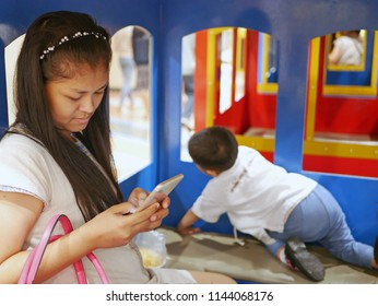 Asian mother being obsessive with her mobile phone ignoring and paying no attention to her baby - parent's smart phone addiction
