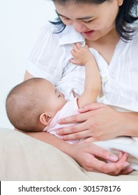 Asian mother breastfeeding her baby girl