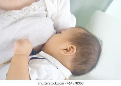Asian mother breastfeeding her baby boy