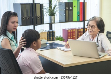 Asian mother came to hospital with patient son meet the old woman doctor talk for sick. Woman and boy meeting doctor in hospital.