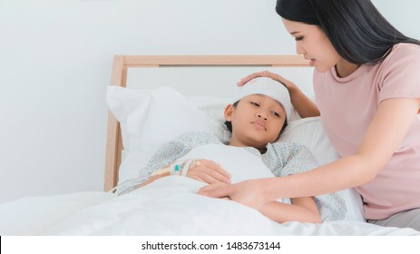 Asian mother caring for daughter injured at head and Stay on bed in the hospital.Concept of caring for the family.