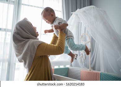 asian mother carry her child from baby crib at home