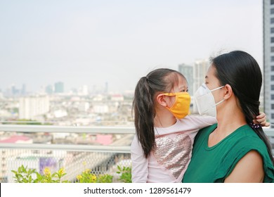 Asian mother carrying her daughter with wearing a protection mask against PM 2.5 air pollution in Bangkok city. Thailand.